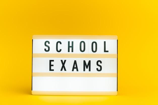 Light box z tekstem, egzaminy szkolne, na żółtej ścianie