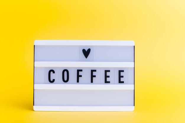 Light box z tekstem, kawa, na żółtej ścianie