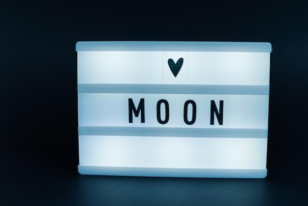 Light box z tekstem, księżyc, nad ciemną ścianą