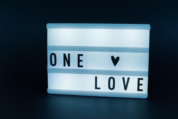 Light box z tekstem, one love, nad ciemną ścianą