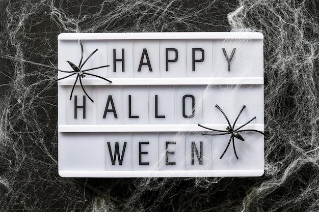 Lightbox z tekstem happy halloween zdobione pajęczyny i pająki, zbliżenie. halloween