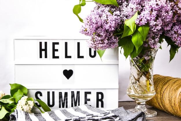 Lightbox z tekstem hello summer i bukietem fioletowych kwiatów bzu w szklanym wazonie