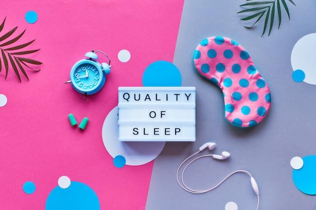 """Lightbox z tekstem """"jakość snu"""". zdrowy sen kreatywne mieszkanie leżał. maska do spania, budzik z niebieskiej mięty, słuchawki, zatyczki do uszu."""
