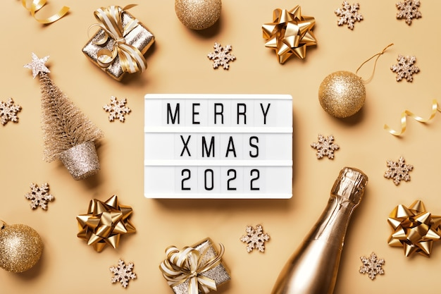 Lightbox z tekstem merry xmas 2022 i złotym świątecznym wystrojem na beżowym tle. kreatywny layout w neutralnych monochromatycznych kolorach