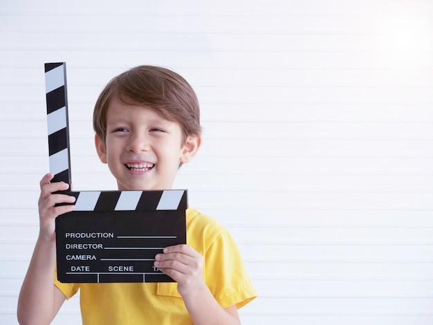 Liitle caucasian chłopiec mienia filme robi clapper desce z uśmiechem.