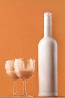 Likier kawowy. biała butelka w kolorze mleka i dwie szklanki z koktajlem kawowym, zdjęcie pionowe.