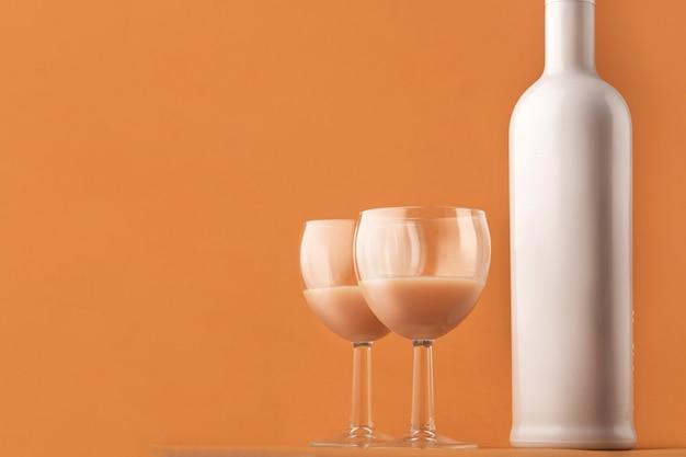 Likier kawowy. biała, mleczna butelka i dwie szklanki z koktajlem kawowym, miejsce na kopię.