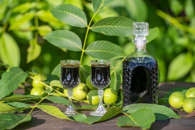 Likier z młodych zielonych orzechów włoskich, środek na ból brzucha, z bliska. nalewka z zielonych orzechów włoskich w szklanej butelce na stole w ogrodzie