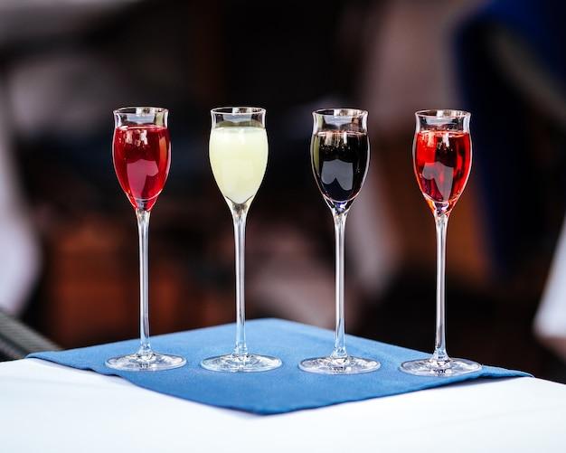 Likiery owocowe w małych szklankach na stole i niebieskiej serwetce