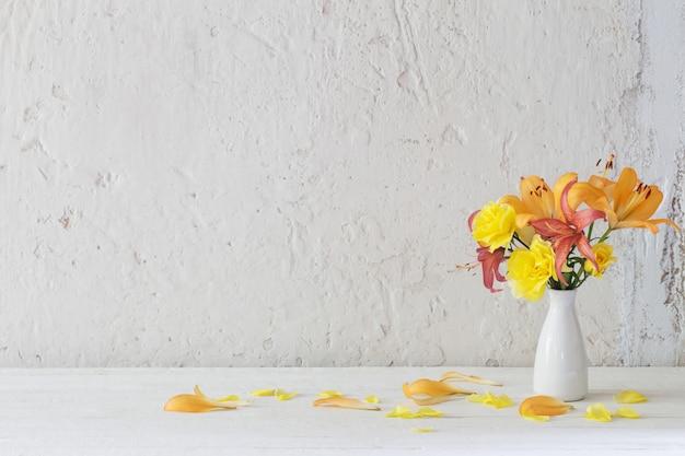 Lilie i róże w białym wazonie na białym tle