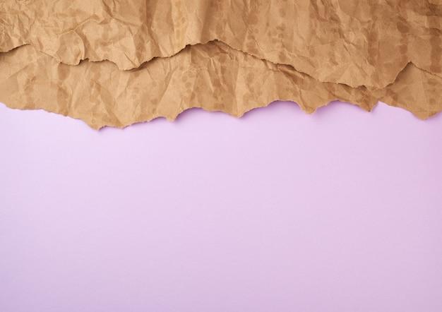 Liliowa powierzchnia z brązowymi elementami z rozdartego papieru