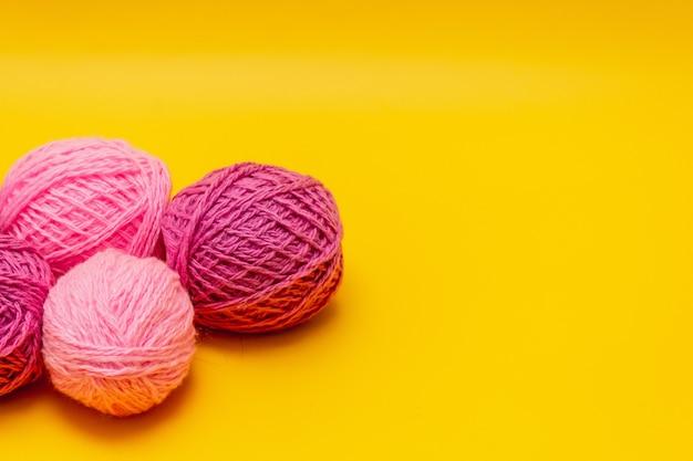 Liliowe, różowe kuleczki wełny leżą na żółtym tle