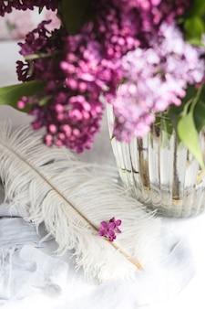 Liliowo-fioletowe kwiaty na białym strusim piórku. liliowe szczęście - kwiat o pięciu płatkach wśród czteroramiennych kwiatów jasnoróżowego bzu (syringa) magia kwiatów bzu o pięciu płatkach.