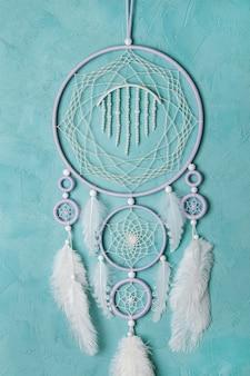 Liliowo-kremowo-biały łapacz snów na akwamarynowej ścianie. skopiuj miejsce na tekst.