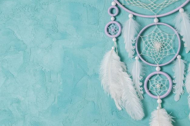 Liliowy kremowy biały łapacz snów na seledynowym tle. skopiuj miejsce na tekst.