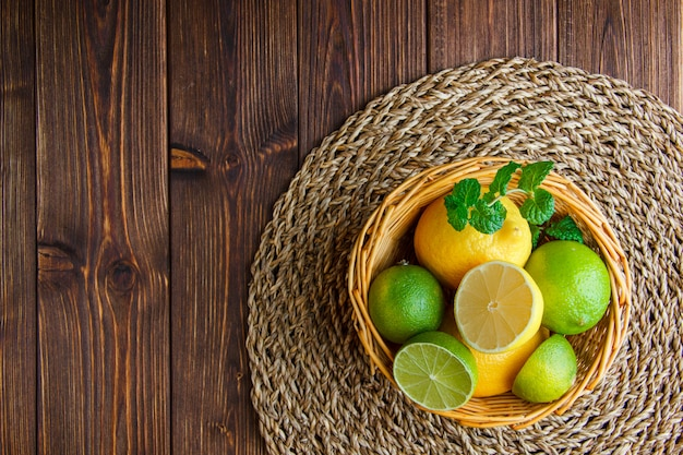 Limonki z cytrynami, zioła w wiklinowym koszu na drewnianym stole