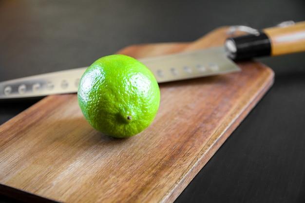 Limonkowy i tradycyjny japoński nóż szefa gyuto na desce do krojenia.