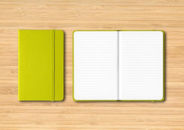 Limonkowy zamknięte i otwarte notebooki pokryte na białym tle na drewnianym stole