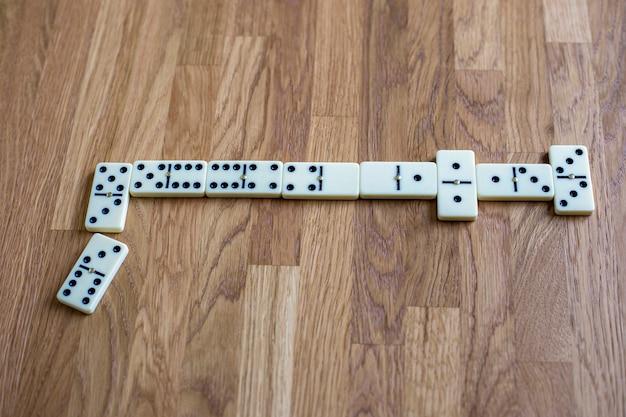 Linia białych domino na drewnianym stole z widokiem z góry na miejsce do gry planszowej na tekst