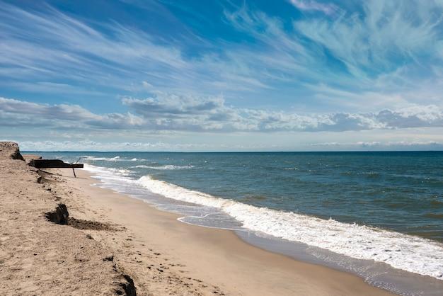 Linia brzegowa ciągnąca się w dal, morze i piaszczysta plaża latem