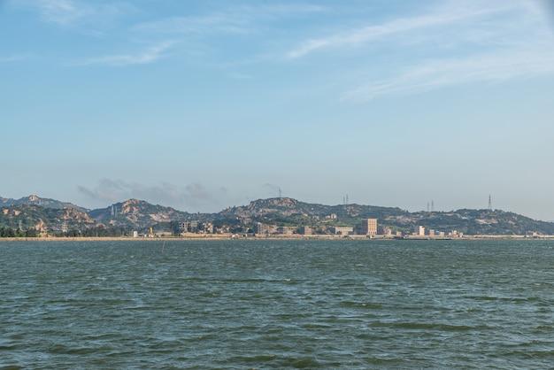 Linia brzegowa pod błękitnym niebem, naprzeciw morza to góry i siła wiatru