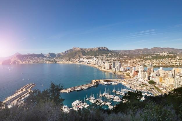 Linia brzegowa śródziemnomorskiego kurortu calpe spain z morzem i jachtami, drapaczami chmur nad jeziorem i górą...