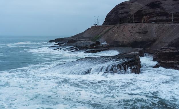 Linia brzegowa w chorrillos lima peru, fale rozpryskujące się i uderzające o skały na plaży la herradura w pochmurny dzień