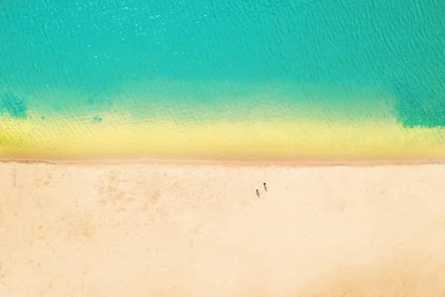 Linia brzegowa z czystą lazurową wodą i żółtym ciepłym piaskiem - koncept morskiej rekreacji i ekoturystyki