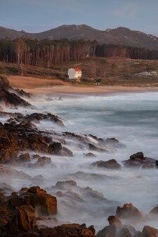 Linia brzegowa z kamieniami na brzegu podczas zachodu słońca