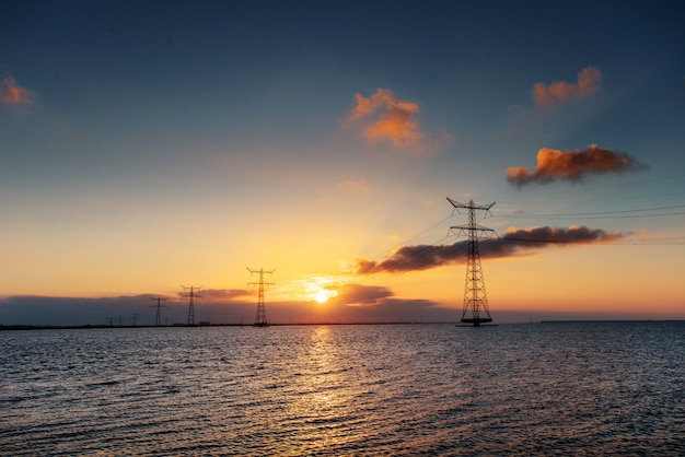 Linia elektryczna nad wodą podczas fantastycznego zachodu słońca