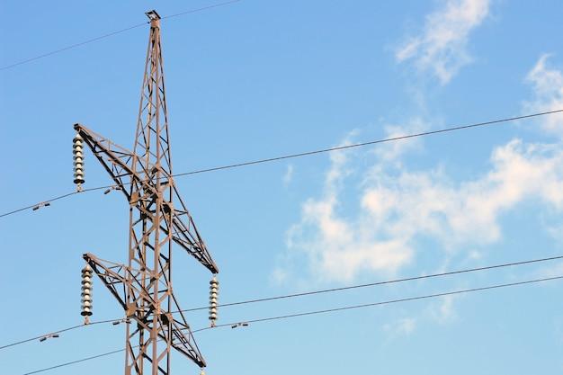 Linia energetyczna na tle błękitnego nieba z chmurami komunikacji przewodowej elektrowni