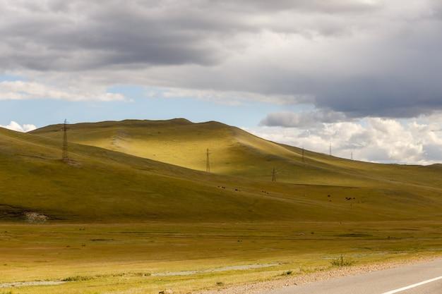 Linia energetyczna wysokiego napięcia biegnie przez wzgórza, mongolia