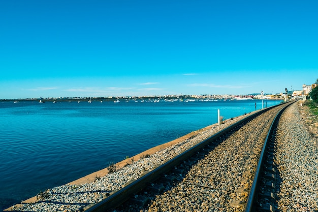 Linia kolejowa faro obok morza.