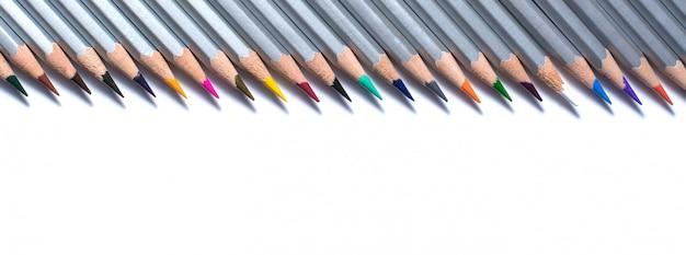 Linia kolorowych ołówków na białej ścianie