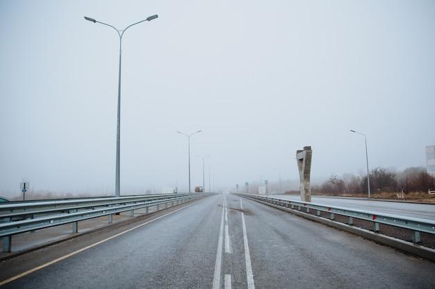 Linia podziału na drodze jest biała, widok z dołu na utwardzoną drogę. oznaczenia drogowe na asfalcie na ulicy.