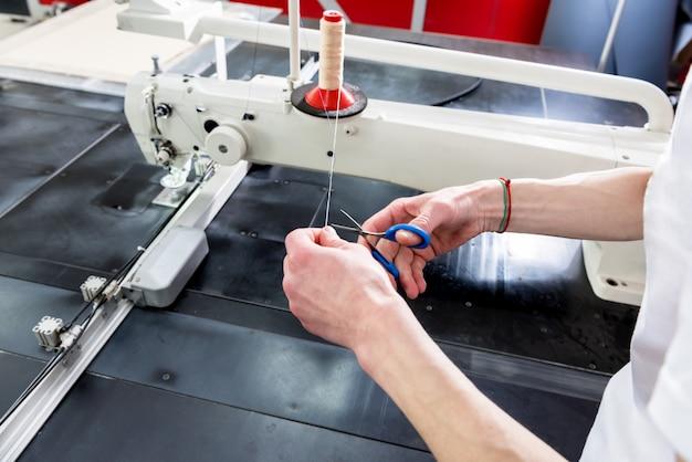 Linia produkcyjna przemysłu tekstylnego. fabryka tekstyliów. pracujący proces szycia