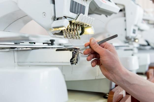 Linia produkcyjna przemysłu tekstylnego. fabryka tekstyliów. robocza szmatka krawiecka. profesjonalna hafciarka. nowoczesny sprzęt