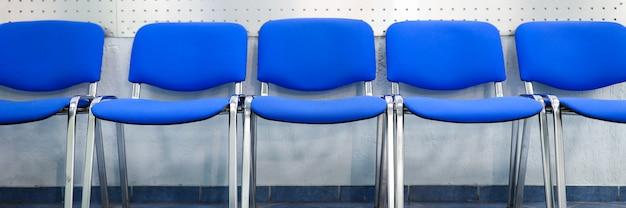 Linia pustych niebieskich krzeseł dla gości stojących przy ścianie w recepcji lub w banku