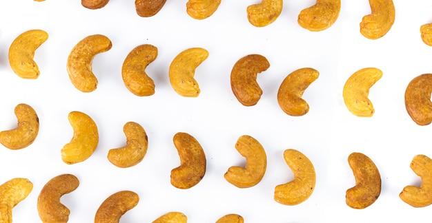 Linia różnego ziarna nerkowca bezszwowy wzór na bielu. orzechy nerkowca to przekąska lub surowiec kucharski. zdrowe jedzenie. niskokaloryczne lub dietetyczne jedzenie.