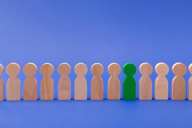 Linia rzędów drewnianych figurek ludzi stojących jeden zielony specjalny