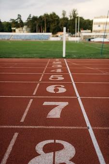 Linia startu do biegania po stadionie, nikt, widok z boku. pusta bieżnia z numerami, powłoka odporna na urazy, nawierzchnia do biegania na arenie sportowej