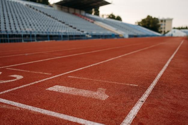 Linia startu do biegania po stadionie, nikt, widok z przodu. pusta bieżnia z numerami, powłoka odporna na urazy, nawierzchnia do biegania na arenie sportowej