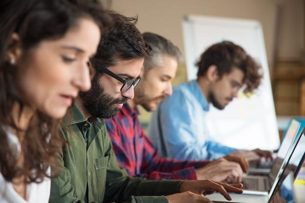 Linia współpracowników korzystających z laptopów w sali szkoleniowej lub klasie