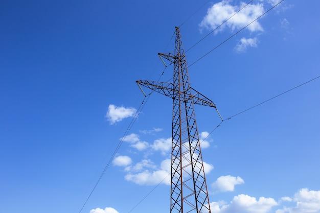 Linie energetyczne, izolatory i przewody. słupy wysokiego napięcia na tle błękitnego nieba i światła słonecznego.