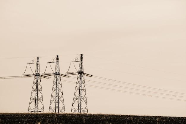 Linie energetyczne na tle nieba zakończenie. sylwetka słup elektryczny z copyspace w odcieniach sepii. przewody wysokiego napięcia nad ziemią. przemysł elektryczny w trybie monochromatycznym.