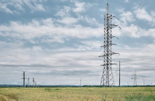 Linie energetyczne wysokiego napięcia, krajobraz na zielonym polu w południe, jasny słoneczny dzień, błękitne niebo z chmurami. zaopatrzenie w energię dla życia miejskiego