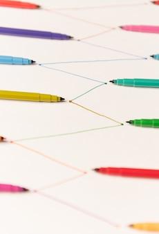 Linie malowane kolorowymi markerami na białym papierze