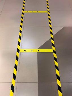 Linie na podłodze wskazujące na potrzebę dystansu społecznego, pandemia covid-19