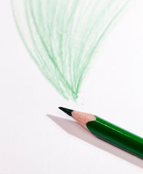 Linie narysowane zielonym ołówkiem na zwykłym papierze słabej jakości, zbliżenie domowej roboty rysunku amatorskiego