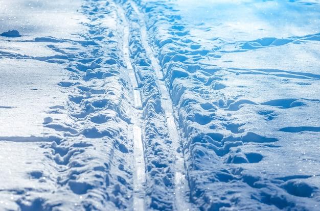 Linie śnieżne wykonane z maszyny naśnieżającej na stoku narciarskim.